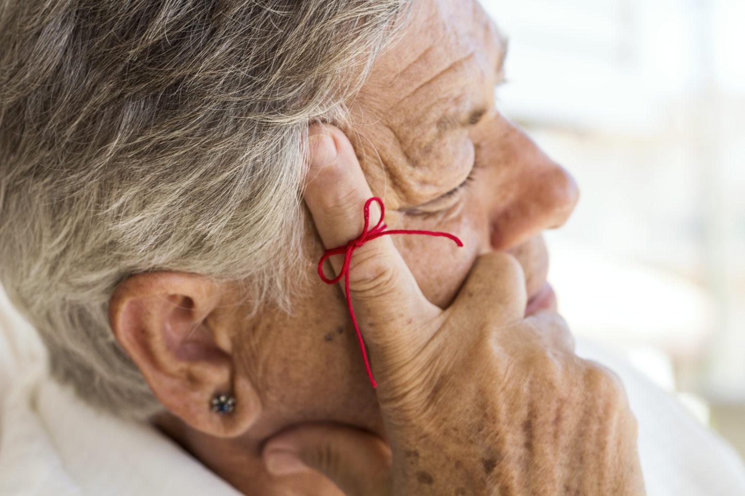 Demenz kranke Frau fasst sich an den Kopf die Angehörigen wissen nicht wie erkennen.