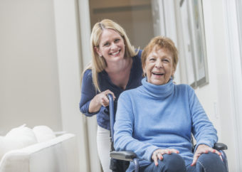 Senior woman in wheelchair with caregiver at home