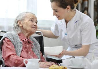 Seniorenbetreuerin kümmert sich um eine Frau im Rollstuhl beim betreuten Wohnen